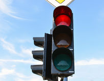 Red color traffic light blue sky in background Stock Photos