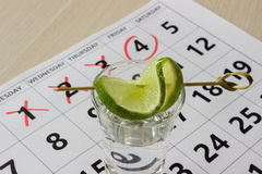 Red color writing on the calendar at friday with shot of tequila with a slice of lime Stock Photos