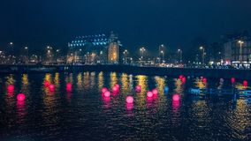 Red colored balls in a canal in Amsterdam in the evening royalty free stock photography