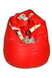 Red colored bean bag with currency notes Stock Images