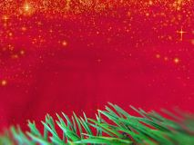 Red colored christmas background with stars falling and Christmas tree branch in green. royalty free stock photo