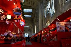 Red colored Christmas market inside railway station and passengers. Royalty Free Stock Photography