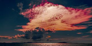 Red colored cirrocumulus cloud, sunset seascape. The Firmament housing a brilliant atmospheric cloudy crimson red sky sunset display over water and through royalty free stock image