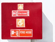 Red colored fire hose cabinet box in front of a white wall royalty free stock photography