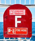 Red colored fire hose cabinet box on a ship royalty free stock image