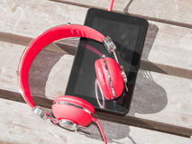 Red colored headphones and tablet PC Royalty Free Stock Image