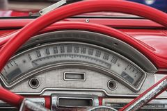 Red colored old american car details, wheel and speedometer. Royalty Free Stock Photos