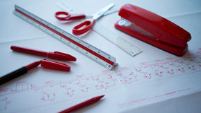 Red-colored pen and accessories on marked up paper Stock Photo