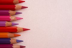 Red colored pencils over a pink background. stock image