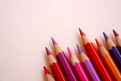 Red colored pencils over a pink background. Red colored pencils are placed in the right corner of the screen royalty free stock photography