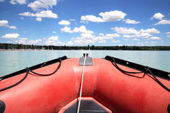 Red colored rubber motor boat floating to harbour haven Stock Photos