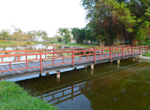 Red colored wooden bridge over the canal in a public garden Royalty Free Stock Photo