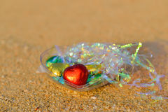 Red and colorful chocolate hearts candies on beach Stock Image