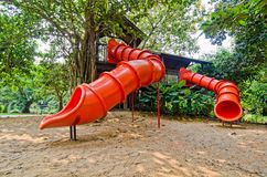 Red colorful slide treehouse garden play area Stock Photo