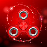 Red colorful spinner on an abstract background. With red luminous backdrop. Abstract background with red luminous backdrop. Modern children`s red toy - spinner Stock Image