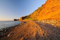 Gravel Beach in the Red of Sunset Royalty Free Stock Images