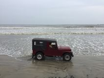 A red colour jeep being driven through a beach at Kunoor. A local driving his red colour jeep through one of the longest drive-in beach in Kunoor Stock Photos