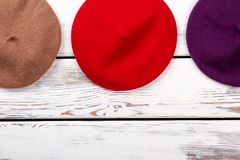 Red colourful berets top view. Flat lay. White wooden background Stock Image