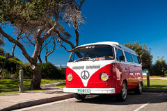 Red Combi Van. A red and white combi van parked at the beach Stock Image