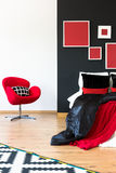 Red chair against white wall. Red comfortable chair with patterned pillow against white wall and king-size bed against black wall Royalty Free Stock Image
