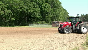 Red Commercial Tractor Pulling Plow in Dirt Field stock video