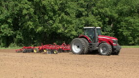 Red Commercial Tractor Pulling Plow in Dirt Field Sunny Day stock footage