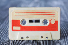 Red compact cassette with magnetic tape format for audio recording and playback. gray wooden background. Soft focus. Royalty Free Stock Photography
