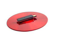 Red compact disc and black removable USB drive Stock Image