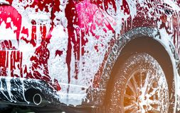 Red compact SUV car with sport and modern design washing with soap. Car covered with white foam. Car care service business concept. Car wash with foam before stock photography