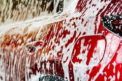 Red compact SUV car with sport and modern design washing with soap. Car covered with white foam. Car care service business concept. Car wash with foam before stock photos