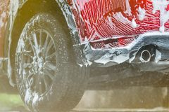 Red compact SUV car with sport and modern design washing with soap. Car covered with white foam. Car care service business concept. Car wash with foam before stock image