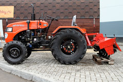 Red compact tractor with a hook-on device for soil treatment. Stock Photos