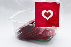 Red condom with heart and a transparent box with a lot of condom Stock Photos