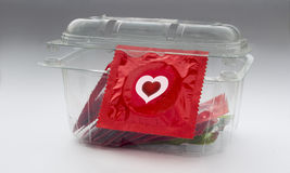 Red condom with heart and a transparent box with a lot of condom Stock Photography
