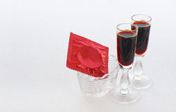 Red condom in a small vase and two glasses with a dark drink Stock Images