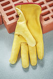 Red construction bricks leather protective gloves on concrete su. Rface building concept Stock Photography