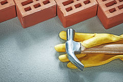 Red construction bricks protective gloves claw hammer on concret. E surface building concept Stock Photos
