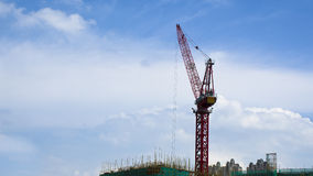 Red construction crane inside building site. Tall tower crane on construction site with blue sky background Stock Image