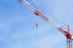 Red construction tower crane on blue sky with white clouds background, detail Stock Photo