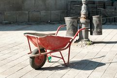 Red construction trolley with pavement stone in the background on the street paving site. Red construction trolley with pavement stone in the background on the Stock Images