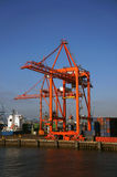 Red Container Loading Crane, Dublin Port. A large red container loading crane surrounded by stacks of different colored containers on the quayside at Dublin Port Royalty Free Stock Images