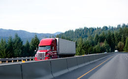 Red contemporary semi truck cargo reefer beside concrete fence d Stock Image