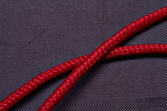 Red cord. Red cord over cloth texture. Synthetic. Close-up royalty free stock images