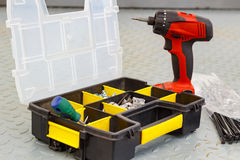 Red cordless screwdriver with screws in a storage box Royalty Free Stock Image