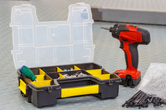 Red cordless screwdriver with screws in a storage box Stock Photos