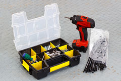 Red cordless screwdriver with screws in a storage box Stock Image