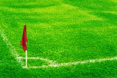 Red corner flag on a football field with bright fresh green turf grass and white soccer touch lines. Stock Photography