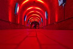 Red corridor. With blueish artwork. View from the floor level. Two people at the far end Royalty Free Stock Photography