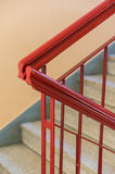 Red corridor handrail. Red painted metal handrails of a staircase in a corridor Stock Photos