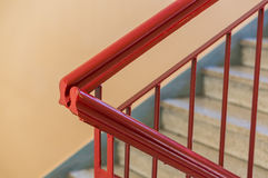 Red corridor handrail. Red painted metal handrails of a staircase in a corridor Royalty Free Stock Photography